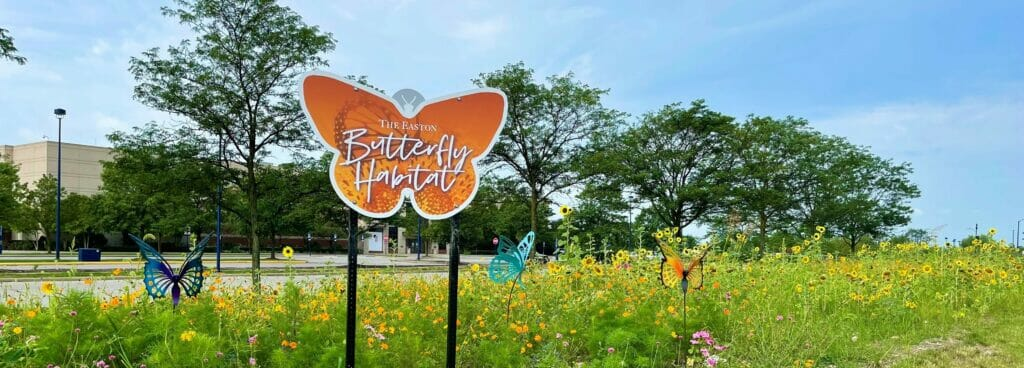 A Butterfly shaped habitat sign in a field of flowers at Easton Town Center.