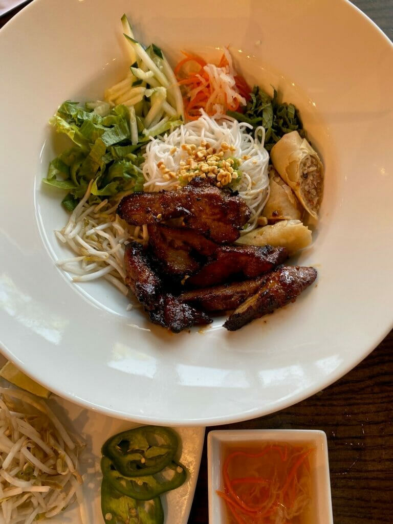 A chicken and rice noodles dish with vegetables and egg rolls in a bowl.
