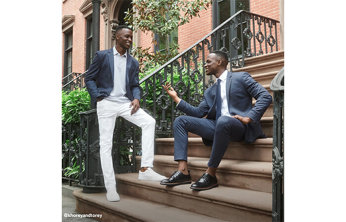 Two men sitting on stairs outside of a building and wearing Express clothing.