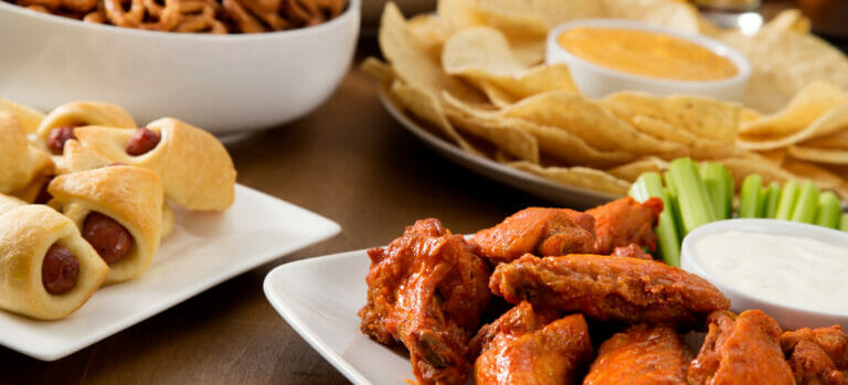 A close up image of a table of snacks that includes pigs in a blanket, chicken wings, celery and ranch dressing, pretzels, and tortilla chips and queso.
