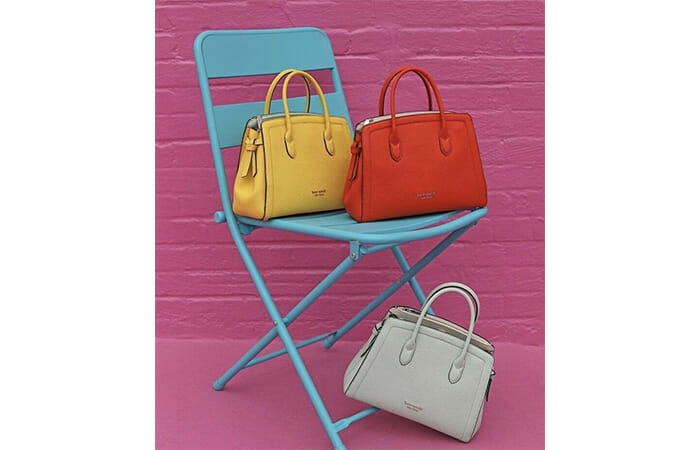 Three different colored Kate Spade bags on a blue chair in front of a pink brick wall.
