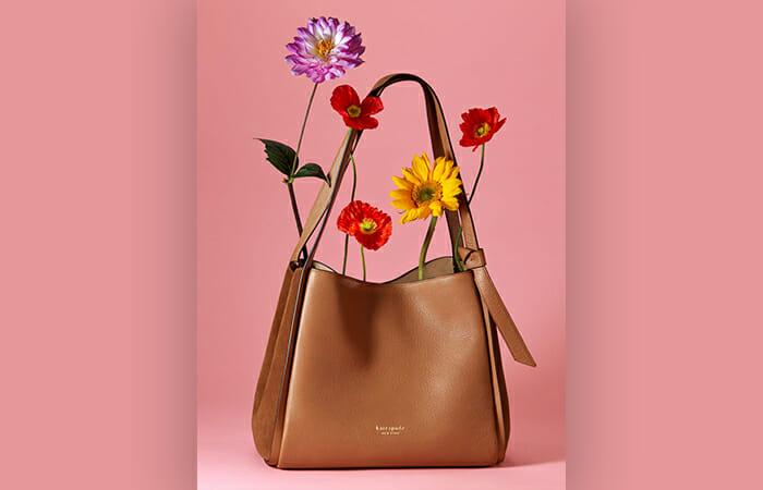 A Kate Spade purse with flowers sticking out of it in front of a plain pink background.