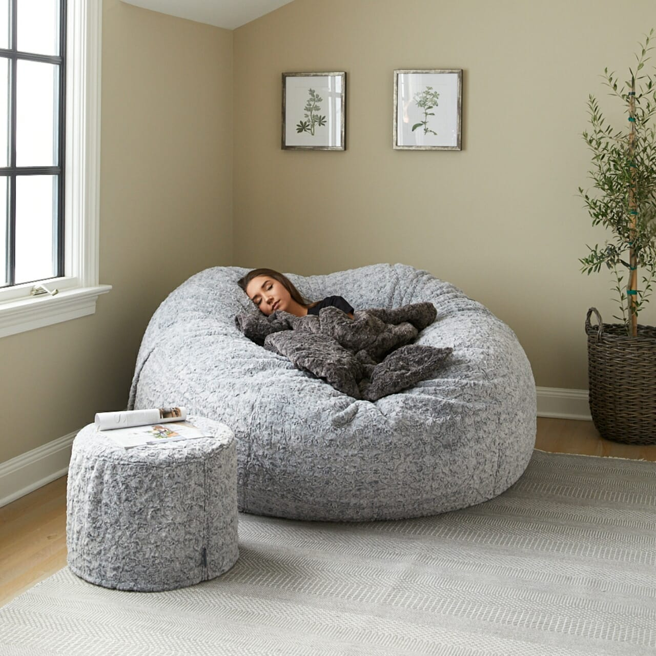 A woman sleeping cozily in a Lovesac Sac Bundle.