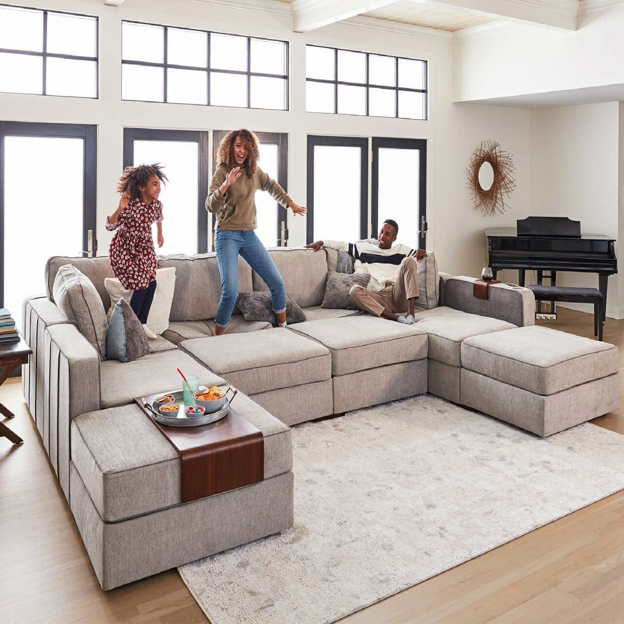 Two kids jumping up and down on a Lovesac Sectional couch.