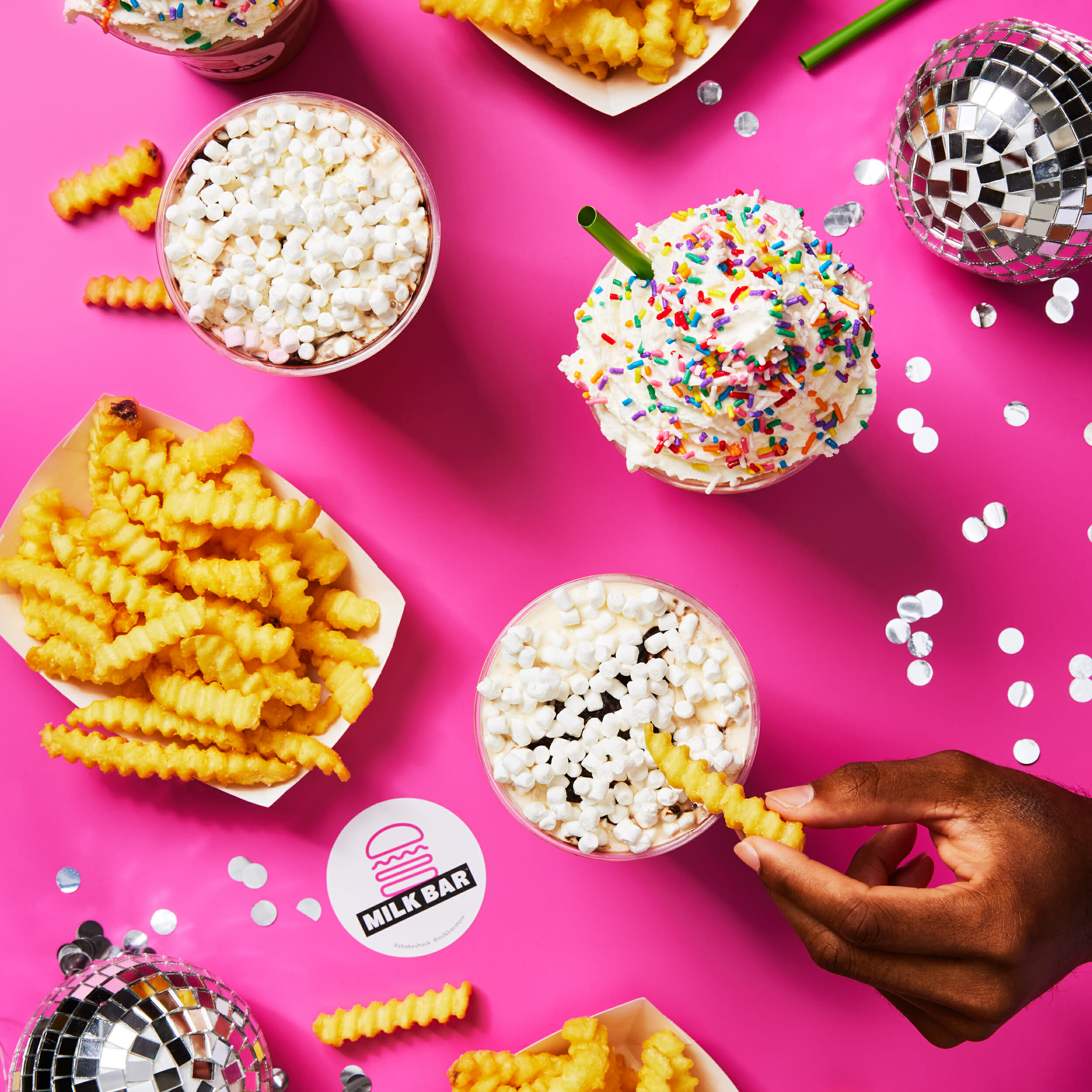 An overhead view of someone's hand grabbing a french fry and dipping it into a milkshake. On the table are a few baskets of fries, some milkshakes, a disco ball, and the Milk Bar logo.