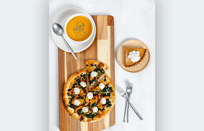 Fall dishes from True Food Kitchen on a cutting board with utensils.