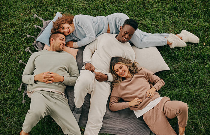 a group of people laying on a blanket and some pillows in the grass while wearing UpWest clothing.