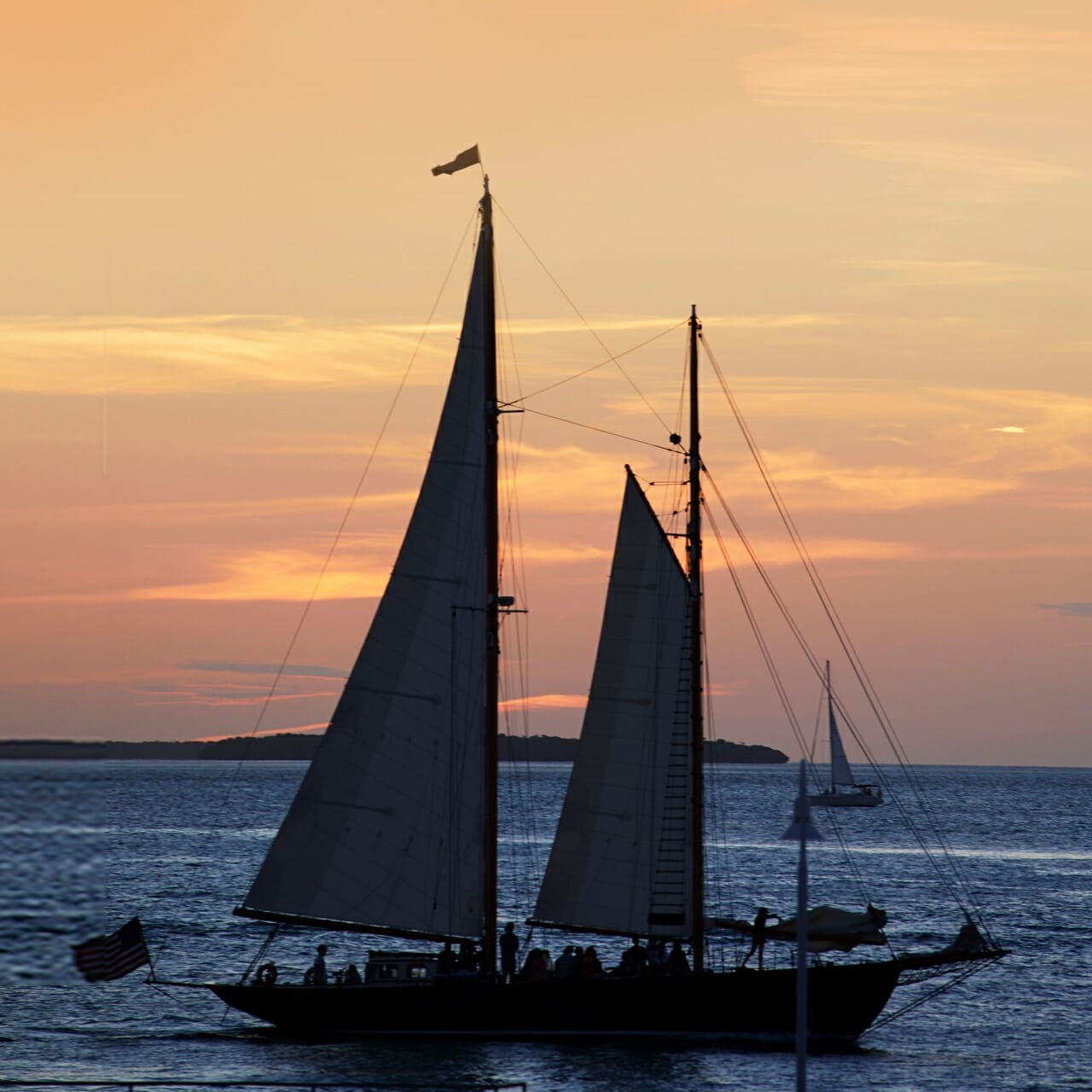 A sail boat on the water at sunset.