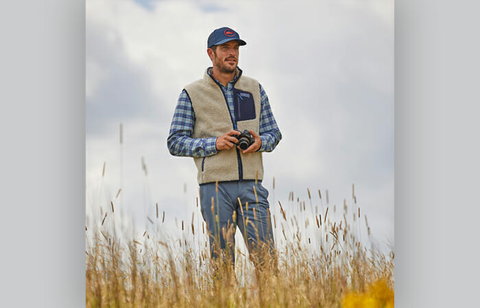 A man standing in a field wearing vineyard vines clothing.