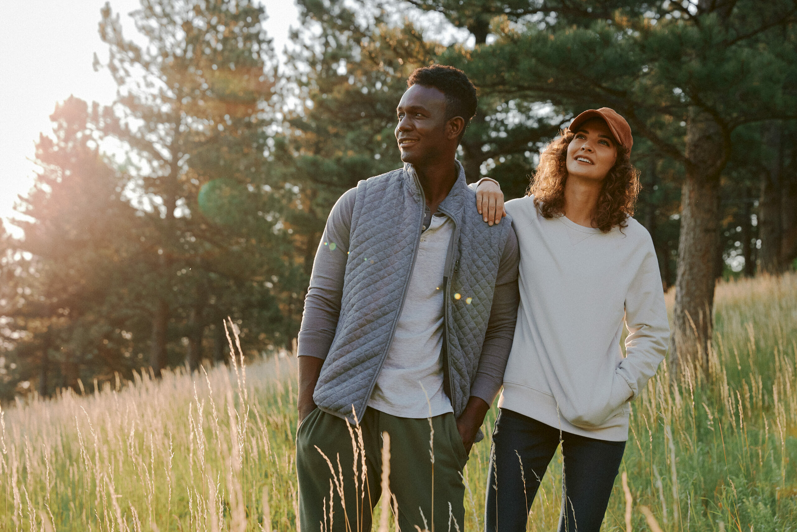 A man and a woman wearing UpWest clothing and standing outside in a field.