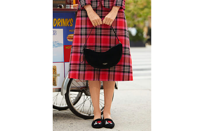 A woman holding a Kate Spade purse while wearing black shoes and a plaid skirt.