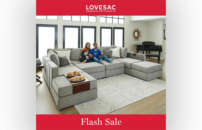 A man and a woman sitting on a Lovesac couch with promotional copy that reads Flash Sale with the Lovesac logo.