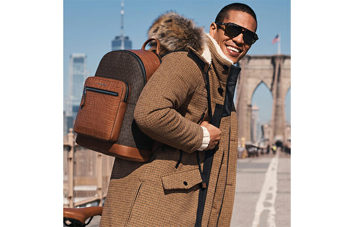 A man in a big coat wearing a Michael Kors backpack in NYC.