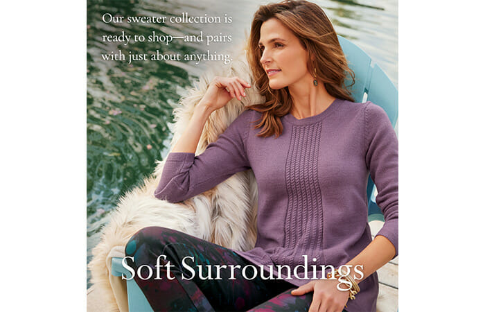 A woman wearing a Soft Surroundings outfit, sitting outside in a chair with promotional copy that reads Our sweater collection is ready to shop - and pairs with just about anything. Soft Surroundings.