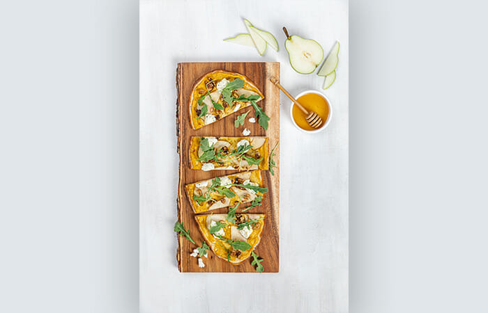 Truffle HOney & Pear Flatbread on a marble slab with honey on the side and a garnish.