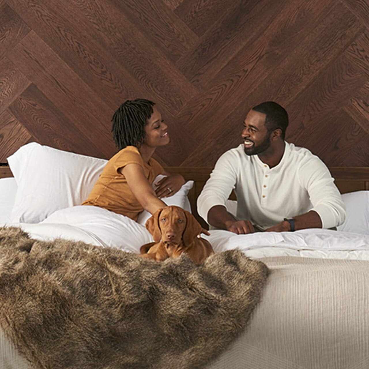 A man and a woman laying in at Tempur-pedic bed with a doggie and cozy blankets around them.