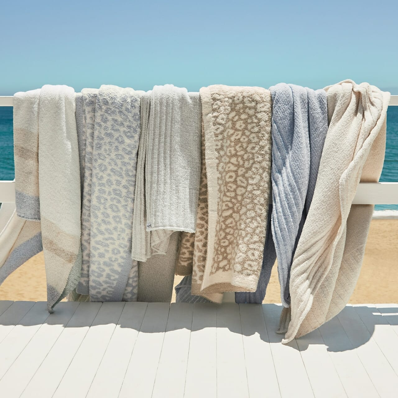 Soft Tommy Bahama blankets on a clothes line with a beach in the background.