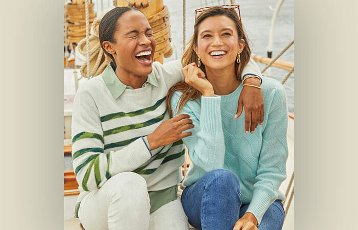 Two women sitting outside and laughing while wearing vineyard vines clothing.